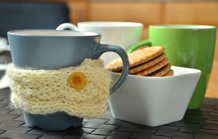Coffee mugs with cup cosy and biscuits