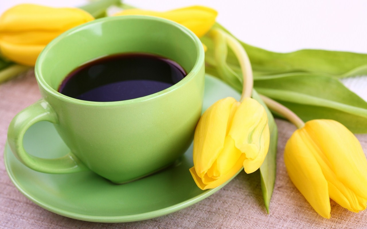 Coffee in green cup and daffodils